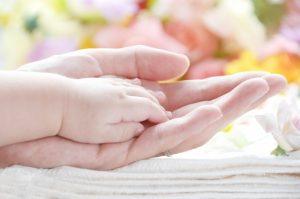 赤ちゃんの手を包む母の手